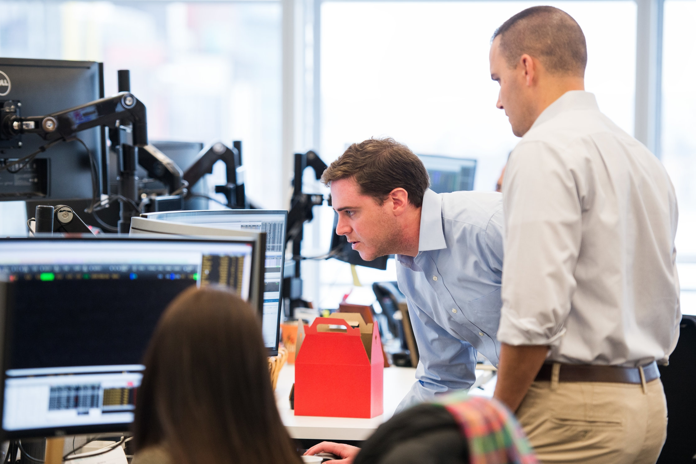 Three Liquidnet employees collaborating at one workstation