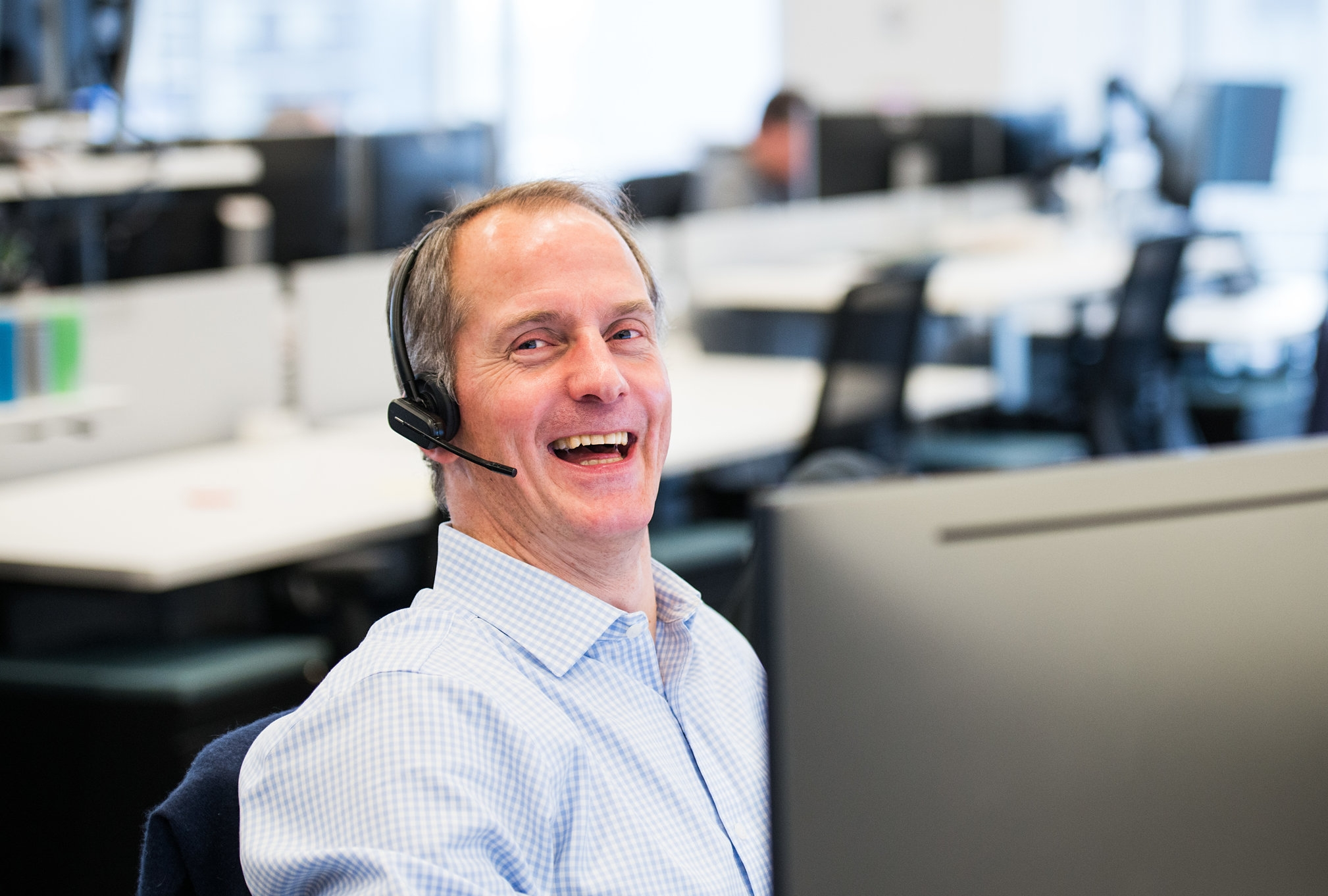 Liquidnet employee with headset smiling at workstation