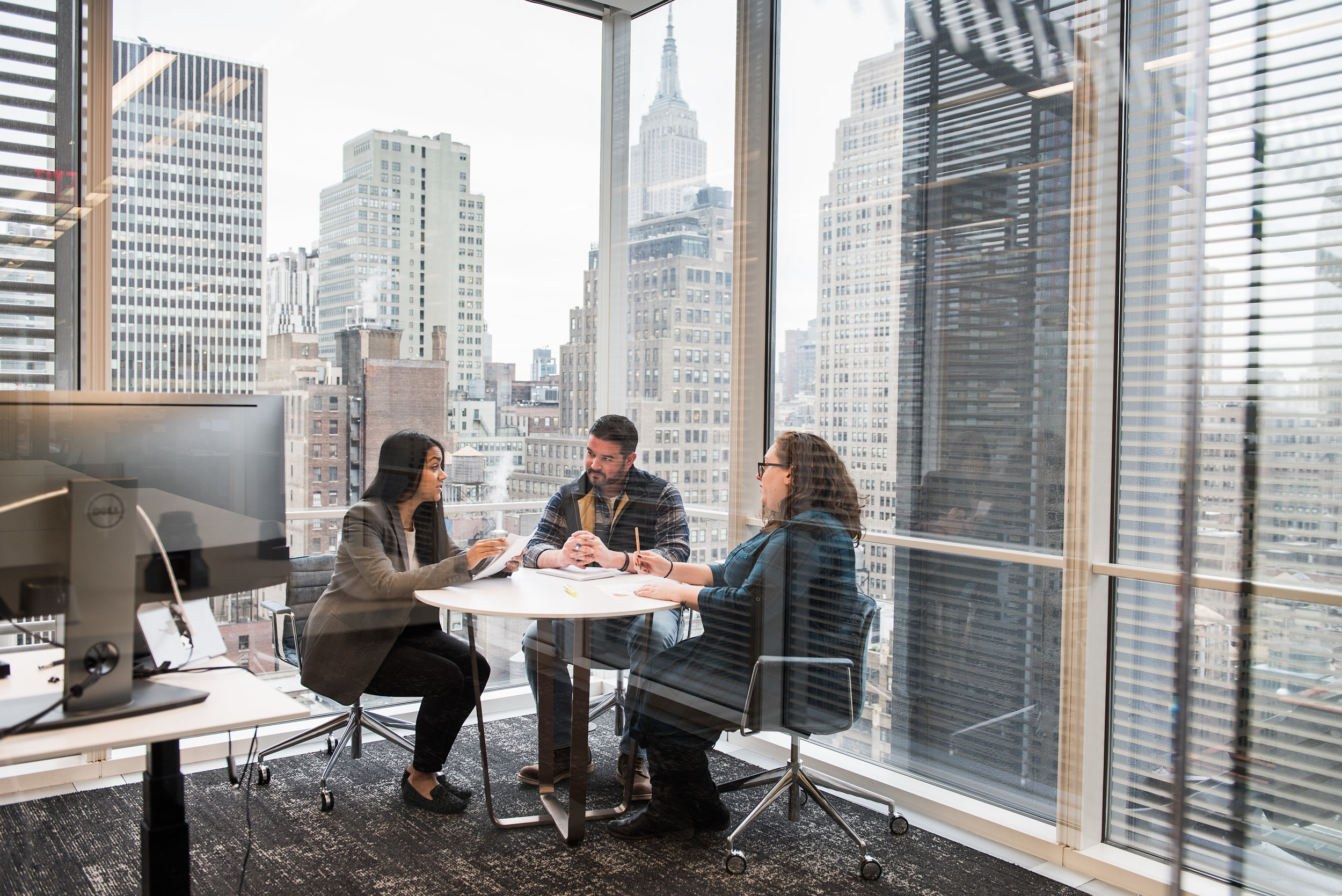 Three Liquidnet employees at small table in corner office