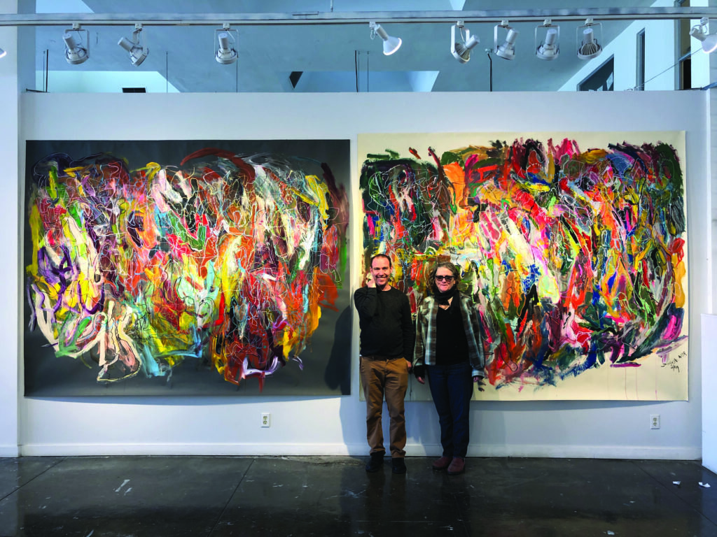 Artist Joseph Alef in front of his paintings with studio instructor Kathleen Henderson.