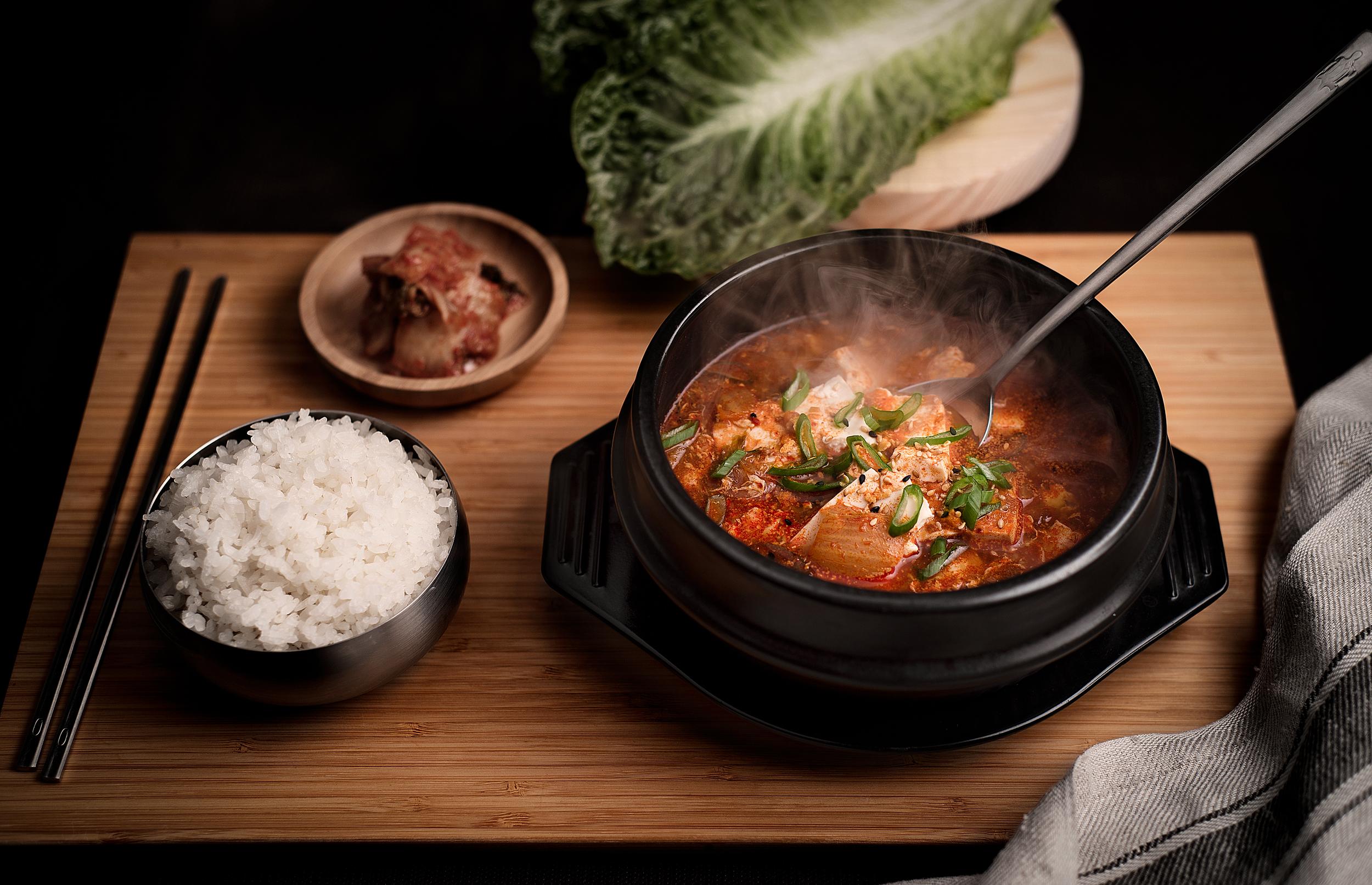 Sundubuchigue - Cazuela hirviente de tofu suave con chirlas y carne de cerdo.Caldo con una combinación de verduras, el suave sabor y textura del tofu, carne de cerdo y chirlas, servido en un cuenco de barro caliente y con una bowl de arroz blanco.Un plato ideal para los que quieren un equilibrio entre lo suave y lo picante sin renunciar a un sabor profundo y redondo. Todo en armonía.11.90€