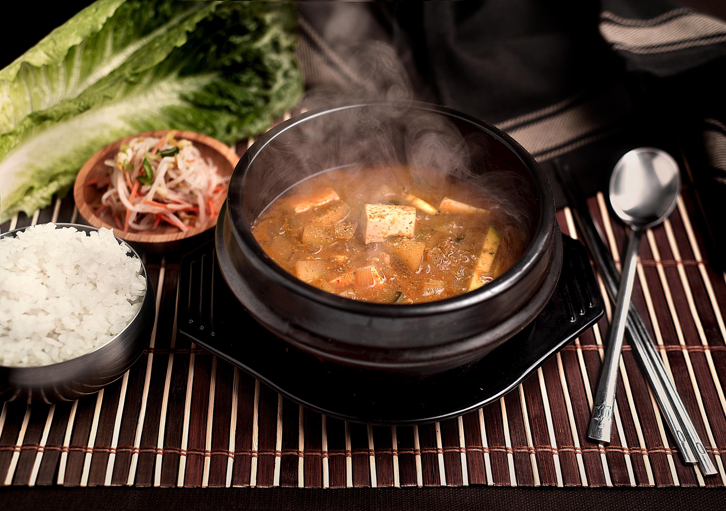 """Duenjangchigue - Cazuela hirviente de caldo de pasta de soja con tofu y verduras.Plato de caldo tradicional coreano hecho de pasta de soja, tofu en trozos, chirlas y verduras varias, servido en un cuenco de barro caliente y un bowl de arroz blanco.La forma perfecta para saborear """"el queso coreano"""" en forma de caldo, un sabor profundo e intenso.11.90€"""