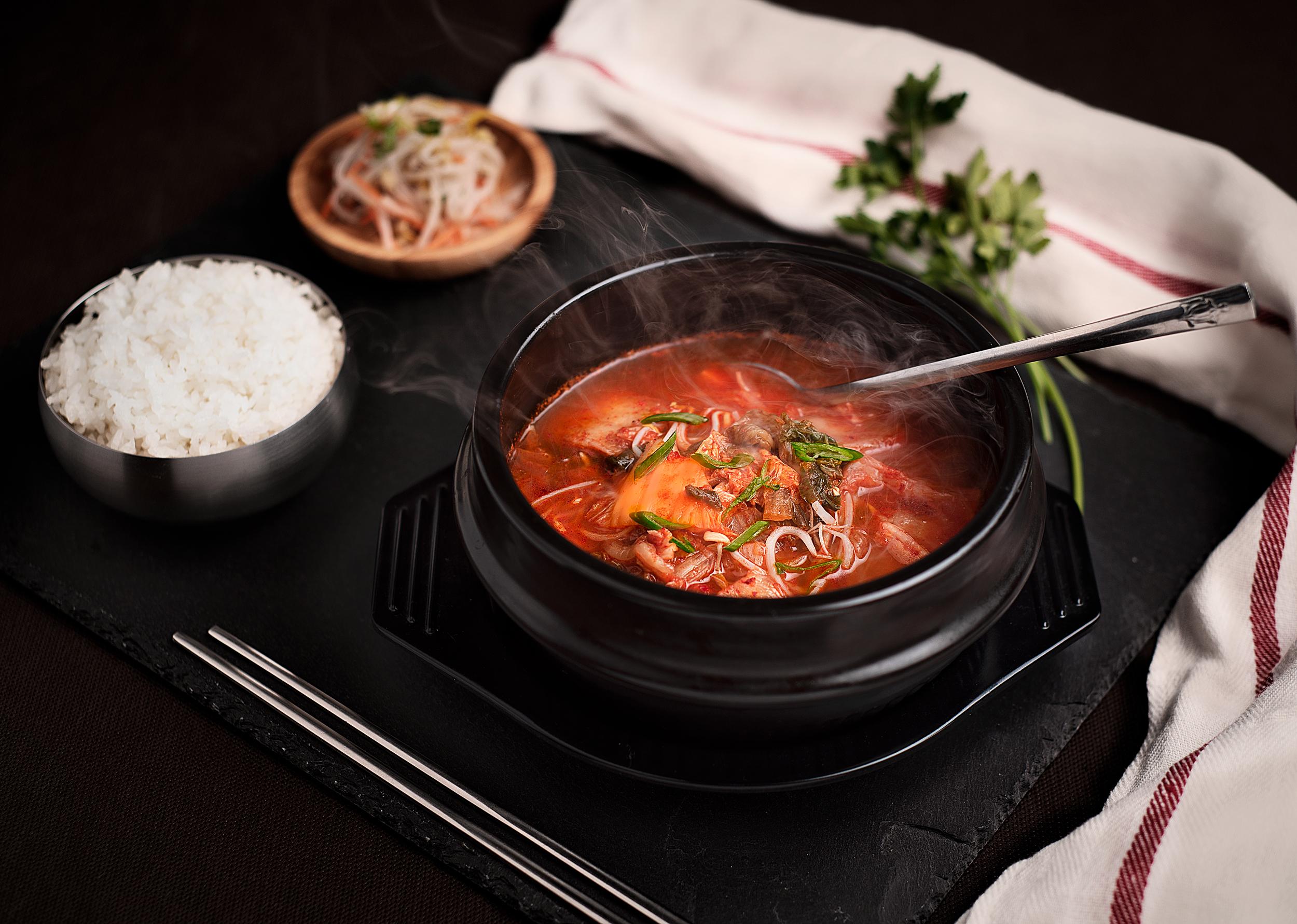 Kimchichigue - Caldo de Kimchi maduro con carne de cerdo y tofu.Quizá el caldo más tradicional coreano junto al Duenjangchigue, es un caldo de Kimchi maduro con tofu y carne de cerdo, con un intenso sabor.Servio en un cuenco de barro hirviente junto a un bowl de arroz blanco. Para los amantes de la auténtica comida coreana.12.50€