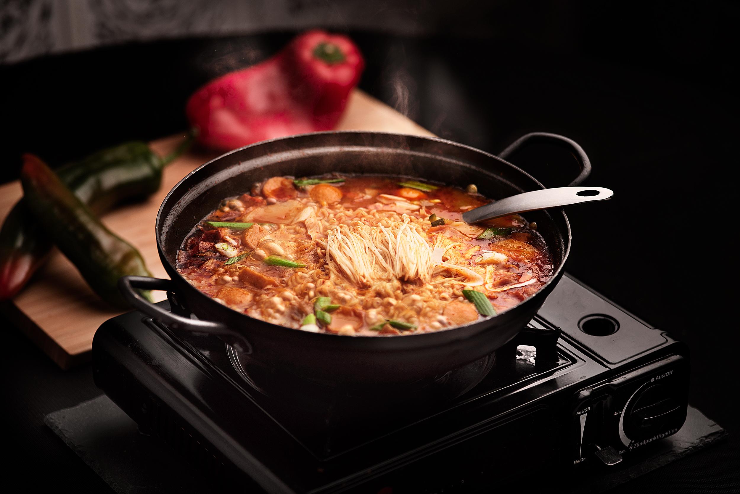 """Budechigue - Cazuela al fuego de caldo de verduras y kimchi, con noodles, salchichas, queso y tofu.La traducción literal del plato quiere decir """"caldo de tropa"""". Plato surgido en la época posguerra civil coreana, se trata de un caldo donde se mezclaban una variedad de ingredientes disponibles a mano. Hoy en día convertido en un plato más refinado, se considera como uno de los platos más populares en Corea.Cazuela grande para 2 personas servida al fuego directo sobre la mesa.25.00€ (Para dos personas)+ 2€ (ración adicional de noodles)"""