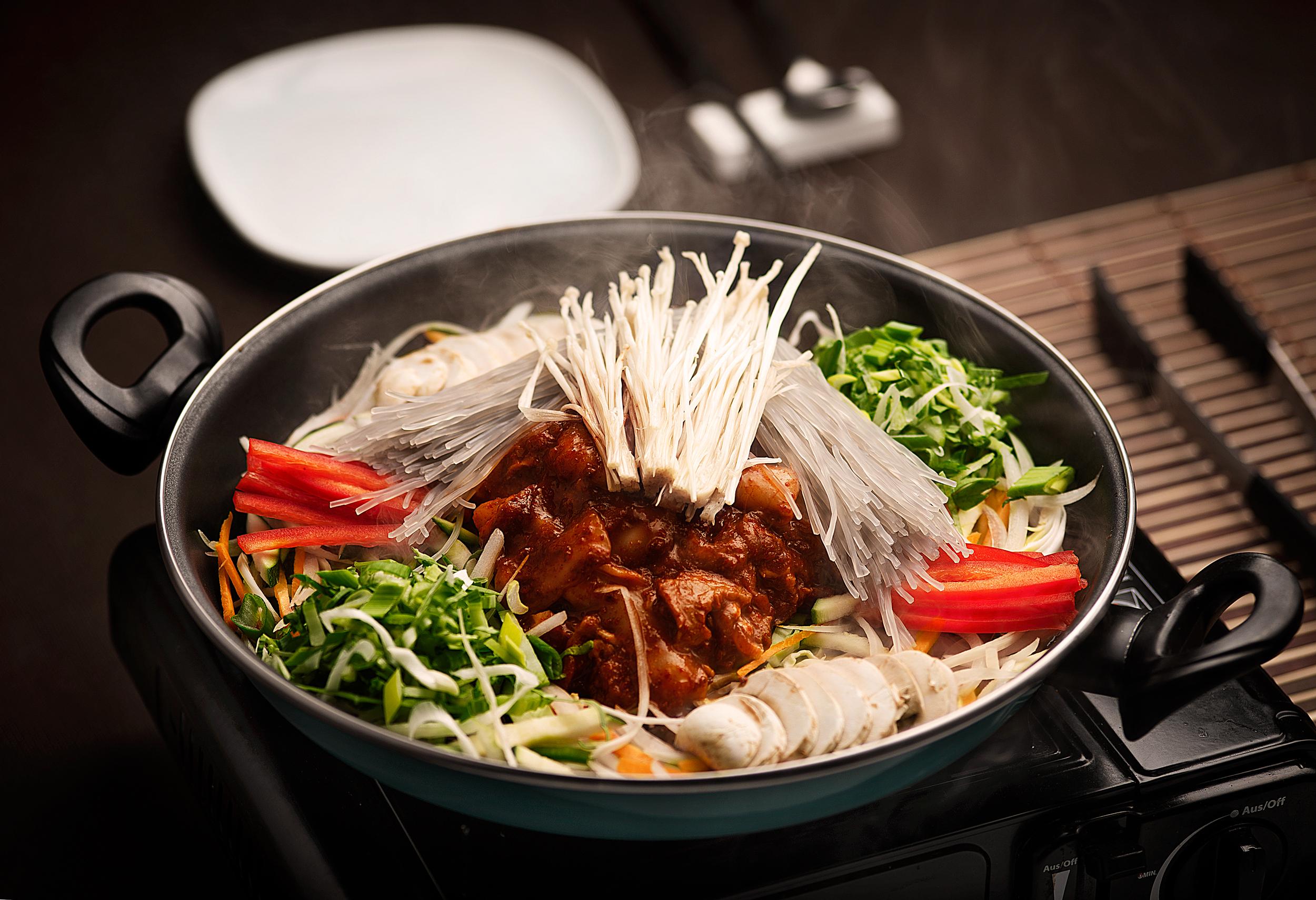 Ojingo Samgyopsal güi - Sartenada caldosa de calamares y de panceta de cerdo con verduras.Una gran sartén para dos personas de calamares y finas tiras de panceta de primera, junto con muchas verduras y salsa picante de la casa. Un espectáculo de plato que se cocina en directo sobre la mesa! Una combinación única entre el marisco y la carne que no te puedes perder.23.90€ (para 2 personas)