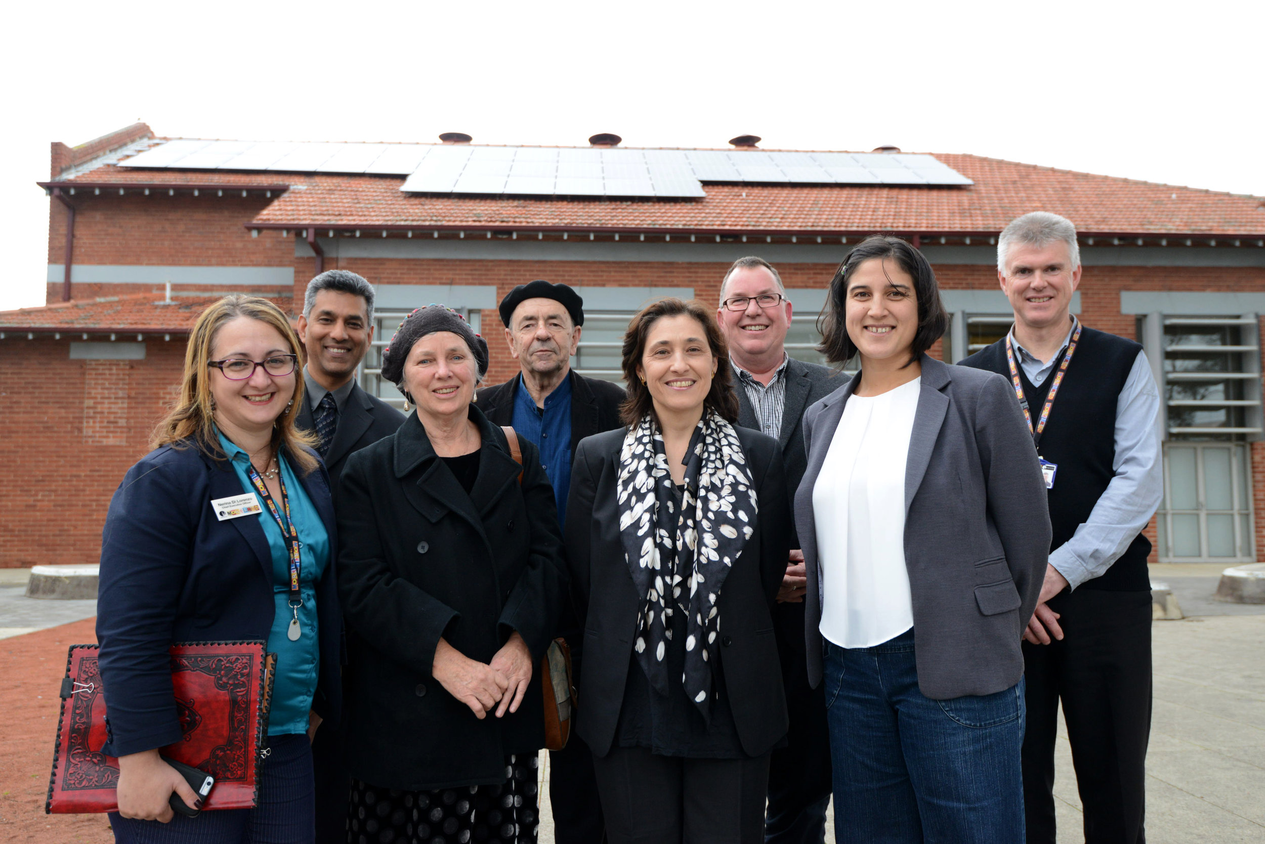 The Hon. Lily D'Ambrosio MP standing outside the Moreland Civic Centre, Coburg with part of the 130kWp array in the background.