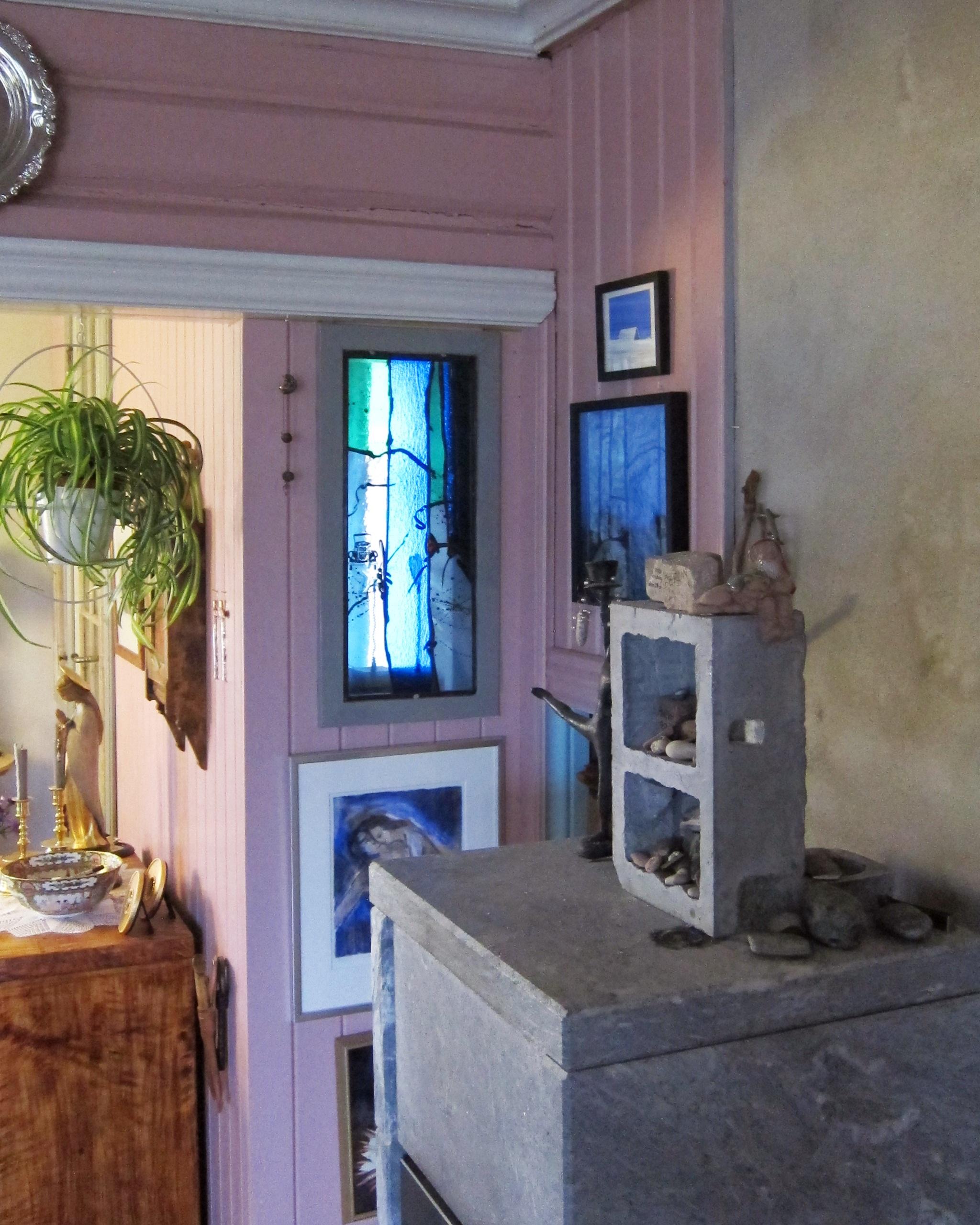 Linjordshagen - En liten åpning i veggen mellom stue og soverom slipper lyset inn til ovnskroken. Med et glassmaleri i noen sterke farger blir det en enda mer levende vegg!