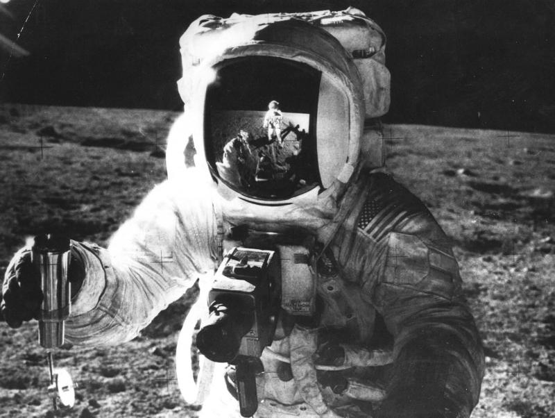 Eén van de Apollo 12 astronauten met een instrument voor het nemen van wetenschappelijk proeven op de maan, 27-11-1969. One of Apollo 12 astronauts with an instrument for scientific tests on the moon. 11-27-1969.