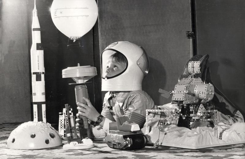 Kinderdromen omstreeks 1969: Jongetje verkleed als astronaut laat een speelgoedluchtballon opstijgen, omringd door onder andere een plastic Saturnusraket en een maanlander gebouwd uit metalen Meccano onderdelen.   A child's dream around 1969: A boy in a child's space suit letting a balloon go up, surrounded by amongst others a plastic Saturn rocket and a lunar module built with metal Meccano parts.