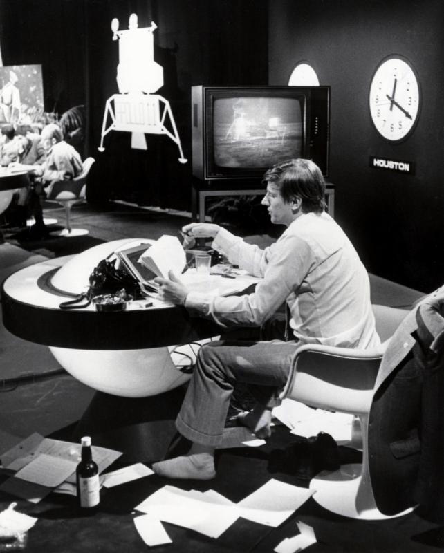 De TV presentator van de maanvlucht, Henk Terlingen, heeft aan het eind van de uitzending zijn schoenen uitgetrokken. 21 juli 1969.  Dutch anchorman Henk Terlingen during the live television show of the flight to the moon has taken of his shoes towards the end of the show. 07-21-1969.