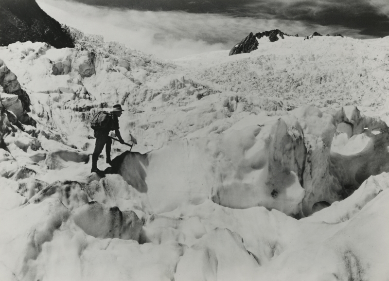 Alpinist op de Franz Jozefgletsjer in Nieuw Zeeland, Zuidereiland. ca.1940. Mountaineer with pickaxe and backpack at the head of the Franz Josef Glacier. New Zealand, South Island, ca. 1940.