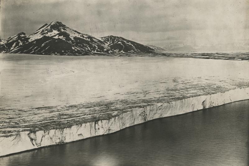 Eén van de eerste luchtfoto' s vanuit een vliegtuig genomen van de IJsfjord en de Boregletsjer op Spitsbergen. Noorwegen, omstreeks 1925. One of the first aerial photos taken from a plane of the mountains and Boreglacier of Spitsbergen. Norway, about 1925.