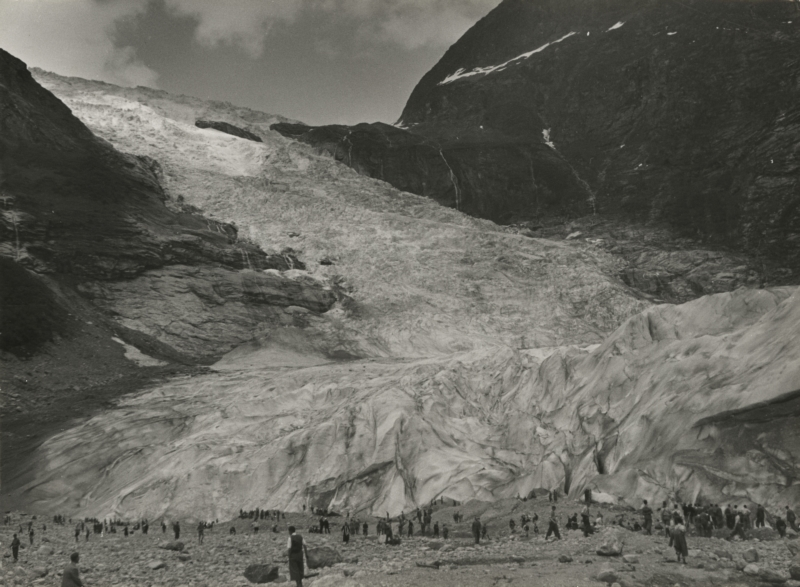 """In 1935 reisden 565 jongens en hun begeleiders naar de Noorse fjorden op het """"kampeerschip"""" de Tarakan. Hier staan ze onder aan de immense Boja Brae gletsjer. Noorwegen, Fjaerland, 1935. In 1953 565 boys and their guides made a trip on the ship the Tarakan to the Norwegian fjords. Here they are near the Boja Brae glacier. Norway, Fjaerland, 1935."""