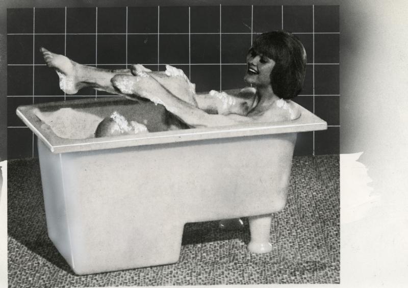 Vrouw badend in schuim in een rechthoekig bad gemaakt van polyetheen, 1964. Woman in bathtube made of polyethene, 1964.