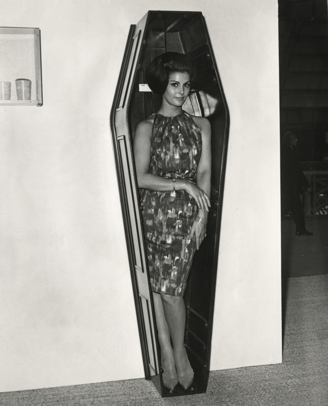 Model Eileen Noble in een doodskist van kunststof, 'The Body' geheten, op de tentoonstelling Interplas 63. Londen, 1963. Model Eileen Noble in a plastic coffin, called 'The Body', on an exhibition. London,1963.