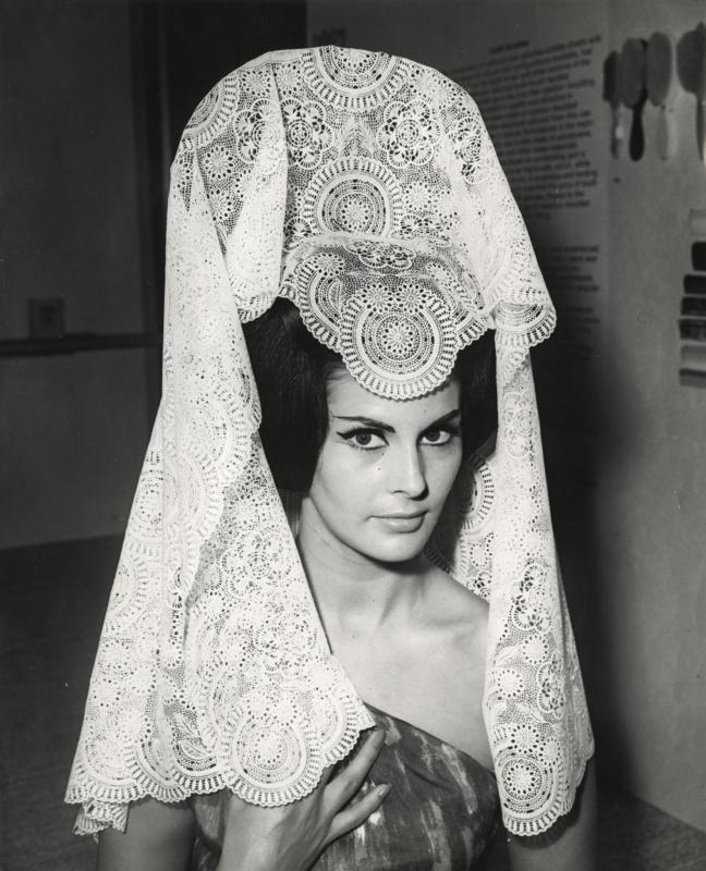 Model Eileen Noble met een kunststof tafelkleed gedragen als een mantilla op een tentoonstelling van kunststof. Londen, 1963. Plastic table cloth worn as a mantilla by model Eileen Noble. London,1963.