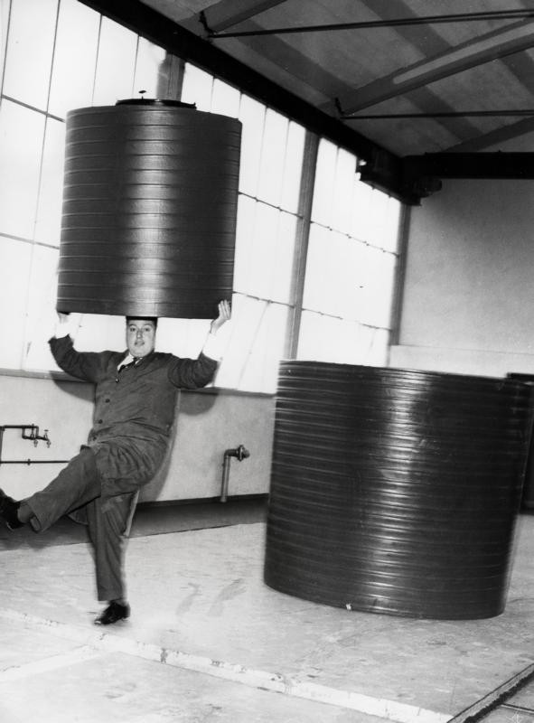 Een werknemer - gekleed in een stofjas - balanceert een kunststof vat (polyetheen) op zijn hoofd. A man balancing a plastic (polyethene) container.