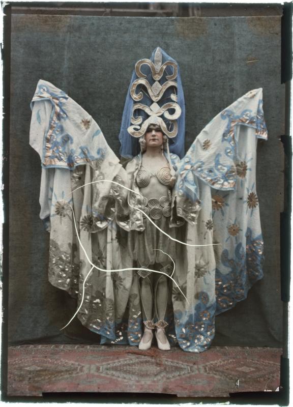 Vlinder. - Leendert Blok (een fotograaf die begin vorige eeuw zijn eigen unieke kleurenprocedé met glasplaten ontwikkelde) werd vooral bekend door zijn zeldzaam mooie bloemenfoto's. Maar ook deze foto van hem vind ik een juweel, niet in het minst doordat het model in vol ornaat - open gevouwen als een vlinder met spelden door haar vleugels - door de fotograaf is vastgelegd.Origineel bijschrift: