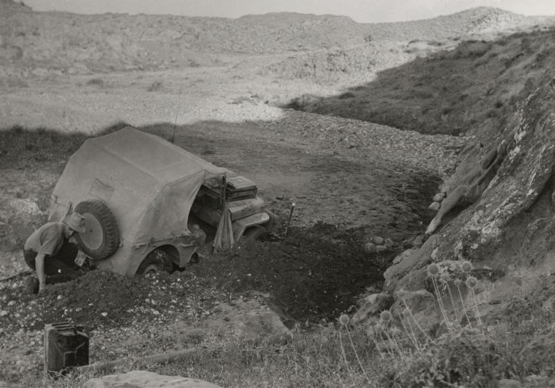 De jeep is vast gelopen in een modderige bedding van een rivier en wordt uitgegraven. Irak, omgeving Kirkoek, 1954. The jeep got stuck in a muddy river bed and is being dug out. Iraq, near Kirkuk, 1954.