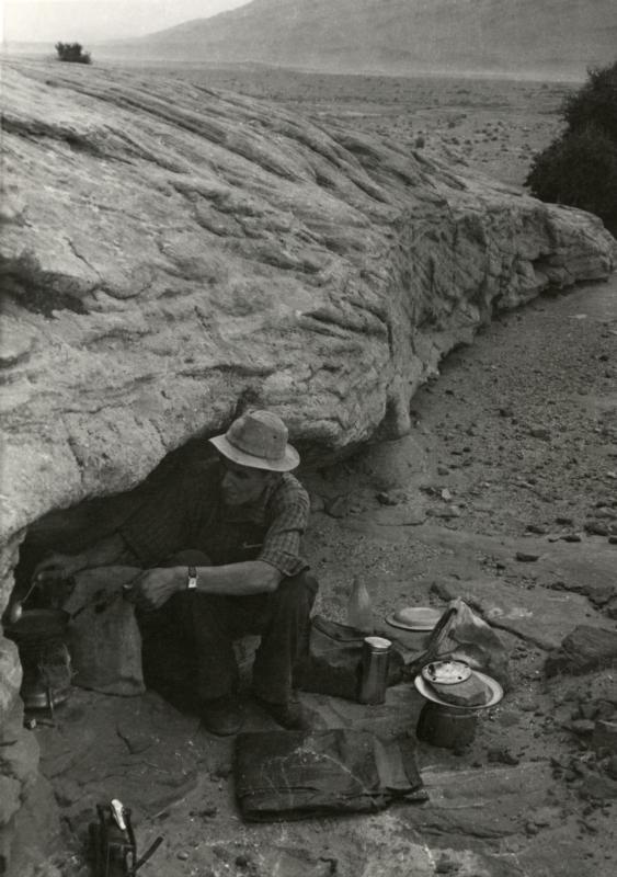 Om zich te beschermen tegen de straffe Sahara wind kookt Jan Glissenaar op zijn primus in een rotsspelonk. Algerije, 1953. To protect himself against the strong Sahara wind Jan Glissenaar is cooking a meal on a primus in a cavern. Algeria, 1953.