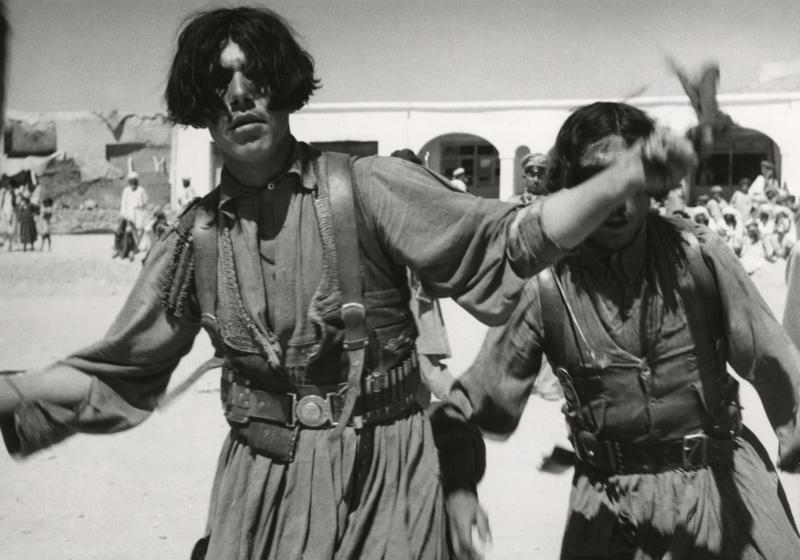 Afghaanse nomaden dansen ter viering van het bevrijdingsfeest. De dansers raakten bezeten door de opzwepende muziek. Afghanistan, Kalat, 1954. Afghan nomads dancing while celebrating the feast of liberation. The dancers are like possessed by the uplifting music. Afghanistan, Kalat, 1954.