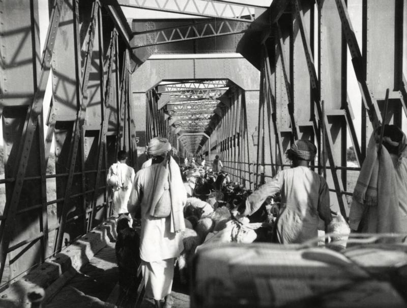Mensen, dieren en voertuigen op een brug over de rivier Chenab. Pakistan, Punjab-gebied, 1955.  People, animals and vehicles crossing the bridge over the Chenab River, Pakistan, Punjab region, 1955.