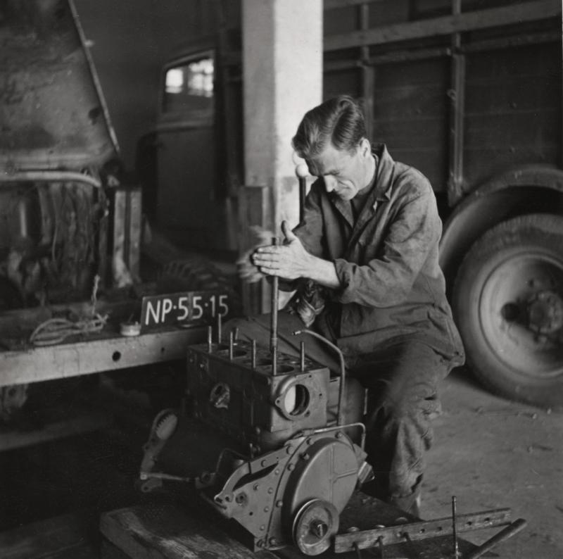 Fotograaf Peter Pennarts heeft de motor van de jeep uit elkaar gehaald. Hij schuurt de verbrande kleppen bij. Libanon, Beiroet, 1954. Photographer Petter Pennarts has taken the engine of the jeep apart. He is sanding the burned valves. Lebanon, Beirut, 1954.