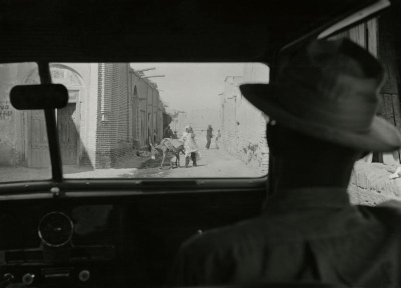 Door de voorruit van de Jeep-Expres een blik op een smalle Perzische straat in een dorp. Iran, 1954. View of a narrow Persian village street seen through the windscreen of the Jeep Expres. Iran, 1954.