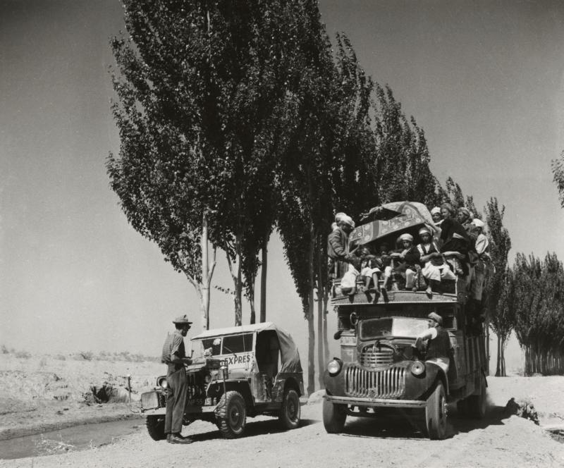 Jan Glissenaar staat voor de jeep die een overvolle vrachtwagen laat passeren met feestgangers. Afghanistan, bij Maimana, 1954. Jan Glissenaar standing in front of the jeep to allow an overloaded truck with celebrators to pass. Afghanistan, Maymana, 1954.