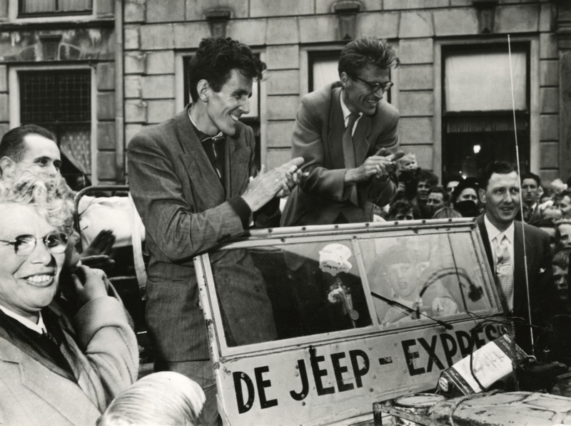 Jan Glissenaar en Peter Pennarts danken voor de kinder-zanghulde bij hun thuiskomst, staande in hun jeep. Nederland, Montfoort, 1955. Jan Glissenaar and Peter Pennarts standing next to their jeep thanking the children for their choral tribute on their return. The Netherlands, Montfoort, 1955.