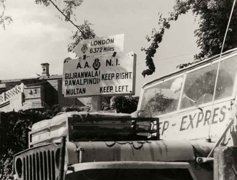 De jeep passeert een verkeersbord in Lahore met de afstand in mijlen naar Londen. Het tweetal is op de terugweg. Pakistan, Lahore, 1955. The jeep passing a traffic sign in Lahore with the distance in miles to London. The two travellers are on their way back. Pakistan, Lahore, 1955.