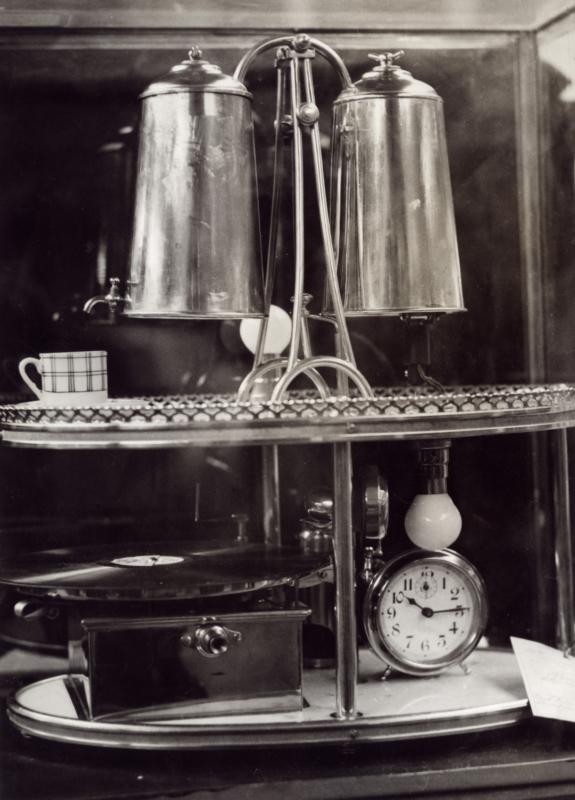 Een tableau om te gebruiken bij het ontwaken. Bovenop bevinden zich twee ketels met een kraantje, waaruit de koffie getapt kan worden. Onderop een grammofoon en een wekker. Parijs, ca. 1932.