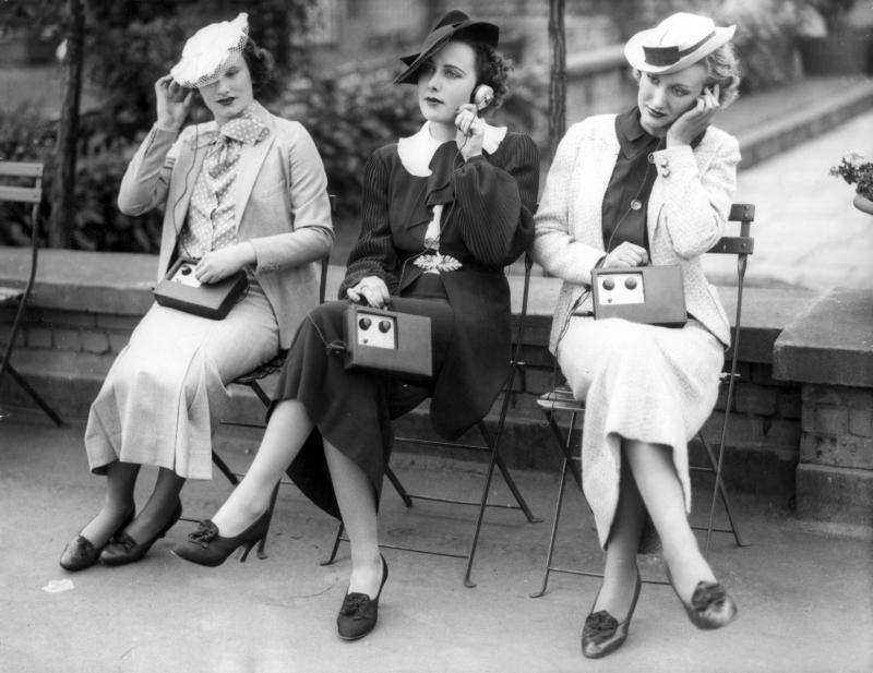 Een handtasradio, uitgerust met twee radiobuizen, waarmee men stations in een omtrek van 80 kilometer kan ontvangen. Drie Londense dames testen het apparaat hier uit. 1936.