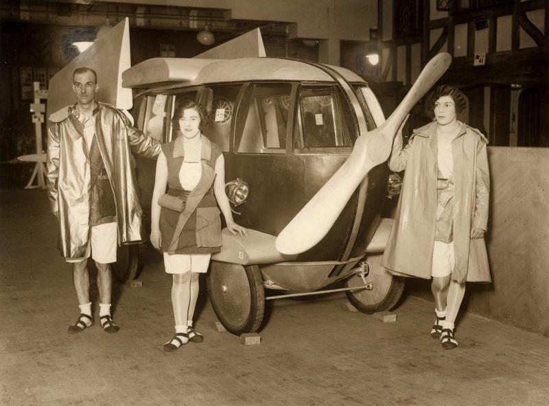 En auto (met uitklapbare vleugels en fikse propeller) en kleding uit het jaar 2000, zoals men het zich voorstelde in 1928.  Car and clothing of the year 2000 as imagined in 1928. (with propeller and the wings outstreched the car is able to fly).