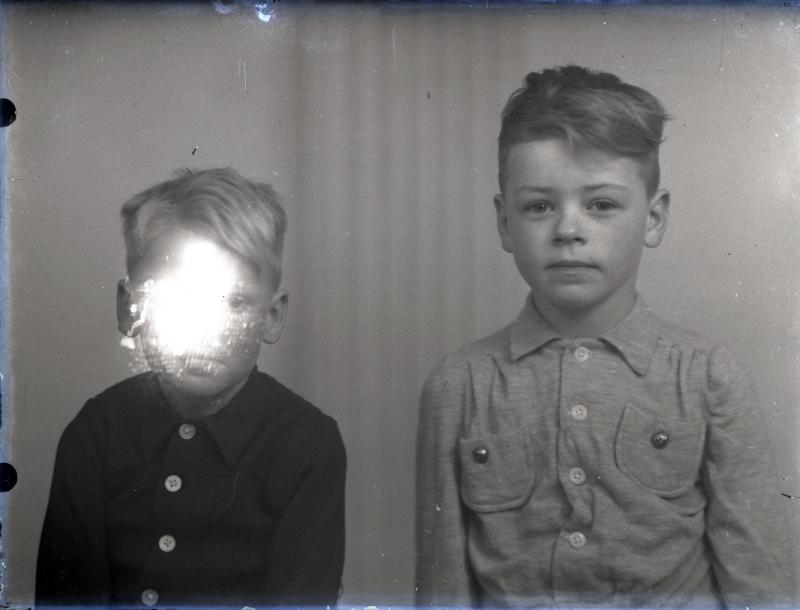 Evolutie. - Portretfotografie Kloosterburen (1930- 1945) - Naarden (2019)Atelierfoto door fietsenmaker/fotograafJacob Molenhuis, Kloosterburen, Groningen, (opname tussen 1930-1945)De atelierfoto's van de beste Hollandse portret-fotografen van dit moment (o.a. Ernst Coppejans, Jitske Schols, Koos Breukel, etc.) blinken niet alleen uit door de pose, het inzicht van de fotograaf, de keuze van de modellen (vaak min of meer bekende personen) maar ook door de ragfijne techniek.Ze zijn perfect belicht, messcherp, scherper dan het oog kan zien, subliem geprint. Kortom van grote klasse. Ik mag dat graag zien, deze evolutie, ook in technische zin, in de fotografie, het medium dat me erg aan het hart gaat. Vanmorgen zocht ik op de beeldbank van het Spaarnestad Archief eveneens naar opmerkelijke portretten, maar dan uit vroegere tijden. Haast onvermijdelijk belandde ik daarbij in de zeer omvangrijke archiefcollectie van de unieke fotograaf Jacob Molenhuis. Nog uit een tijd waarin de perfectie van nu een onbereikbare droom was. Er ging veel mis, het was nog de tijd van glasplaten en stinkende ontwikkelbakken en provisorisch ingerichte donkere kamers. Om over de juiste opslag van het gevoelige materiaal maar te zwijgen. Met soms als resultaat een juweeltje als dit dubbel-lportret van twee onbekende jonge jongens. Mislukt en tegelijk meer dan geslaagd, ik krijg deze foto niet meer van mijn netvlies.