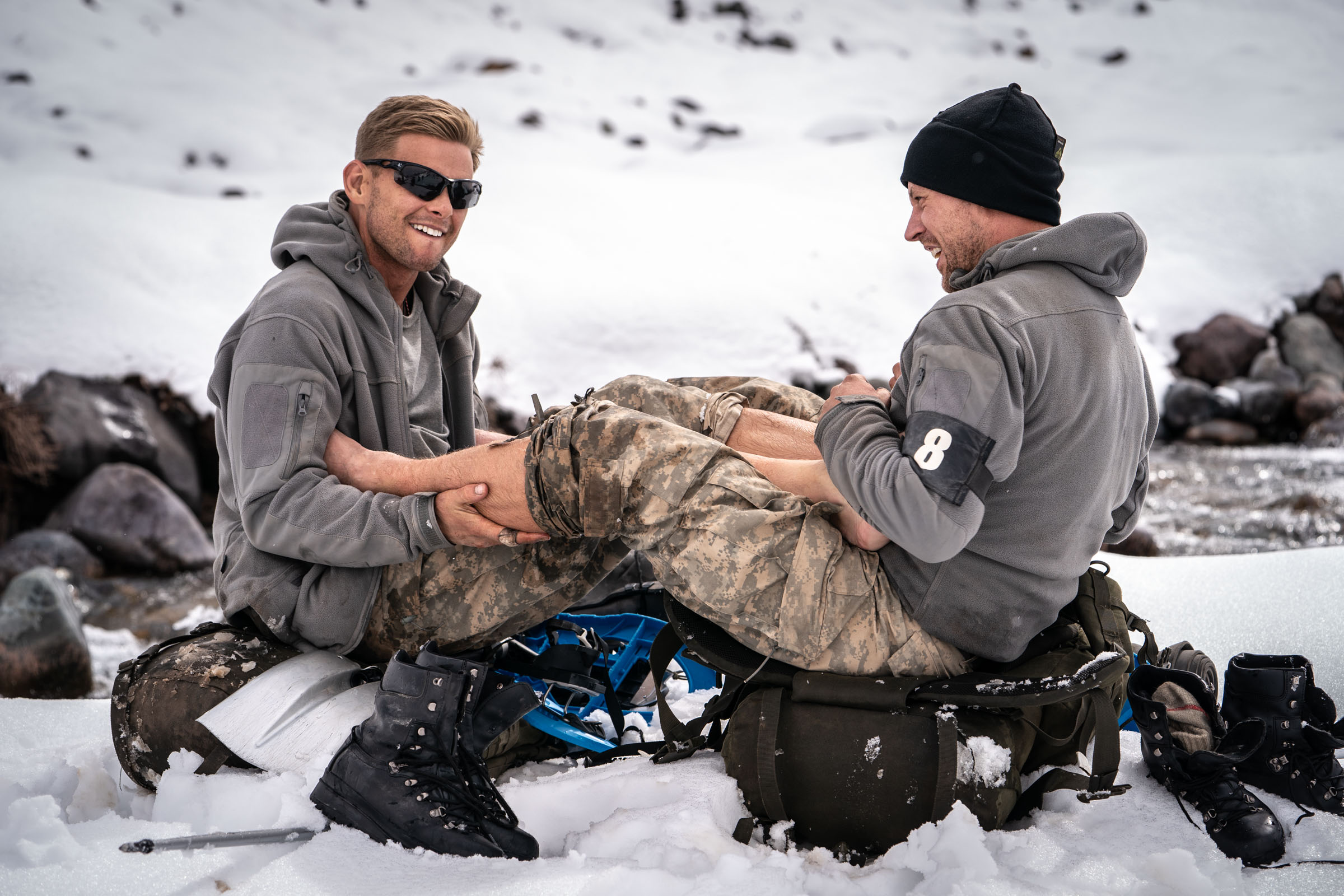 Recruits Jeff Brazier and Wayne Bridge warm each others feet after wading through a freezing stream  Episode 3  Minnow Films / Channel 4