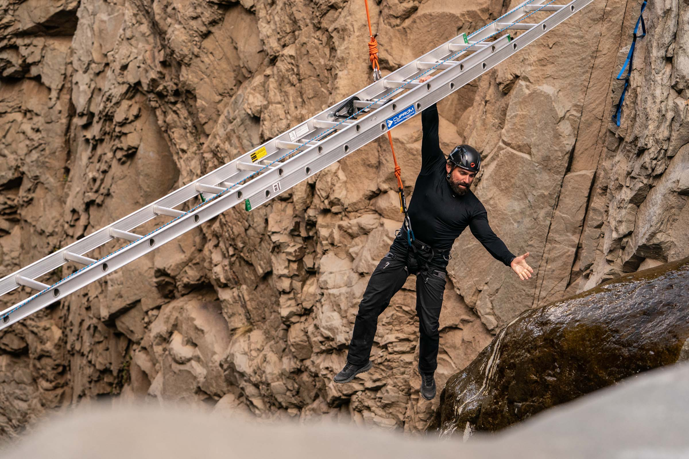 Chief Instructor Ant Middleton holds the ladder with one hand and stops to look down whilst crossing the Devils Throat  Episode 4  Minnow Films / Channel 4
