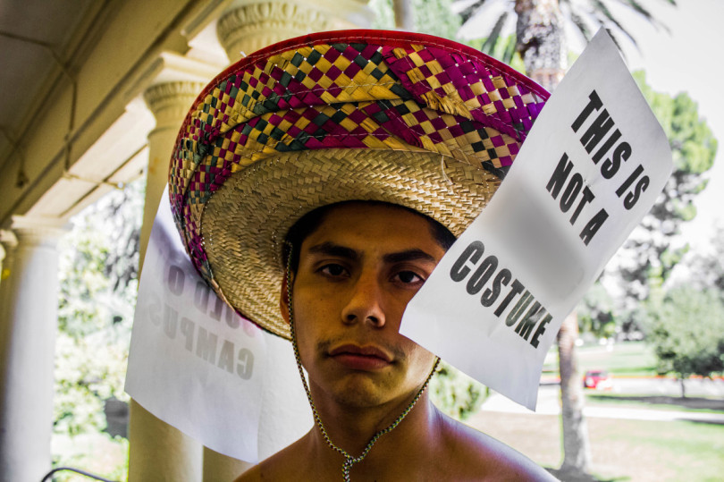 """""""Marcus Garcia, a 20-year-old sophomore at the University of Redlands, wears a sombrero as part of a protest against what he sees as racial insensitivity on campus. This photo was digitally altered to remove an expletive."""" - By   DAVID DOWNEY   