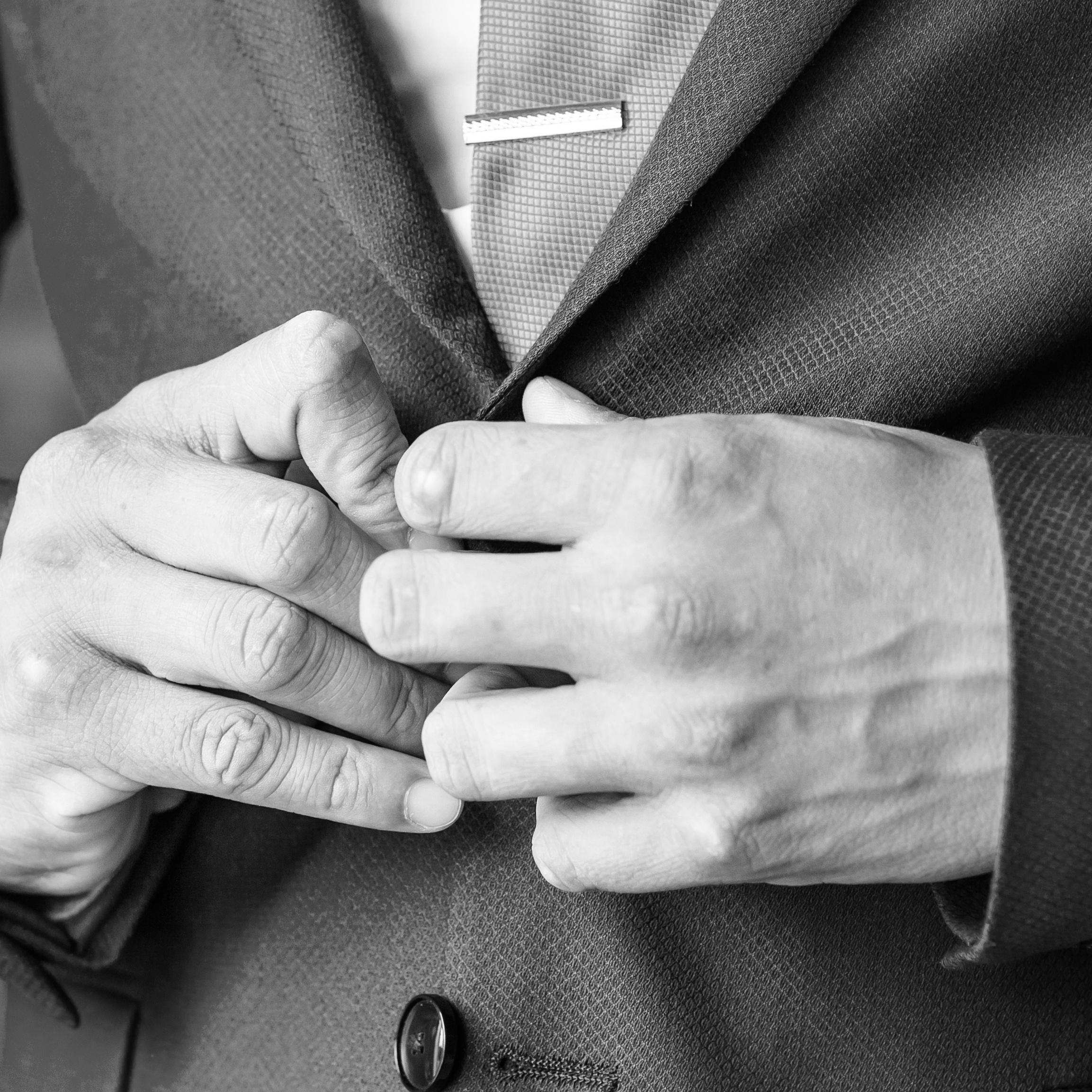 man-buttoning-jacket-close-up-PALE2W4.jpg