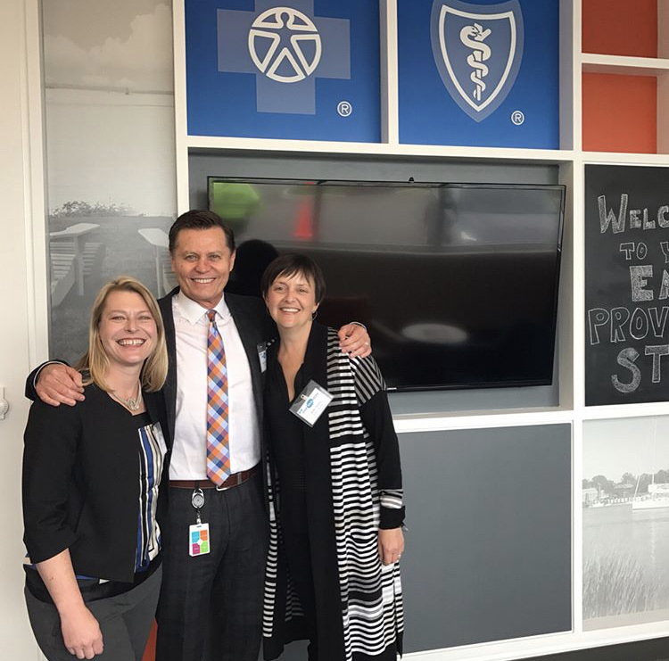 Christine West, Principal of KITE Architects, Philip Hawthorne, Creative Director for BCBSRI and Kelly Taylor celebrate at the grand opening.