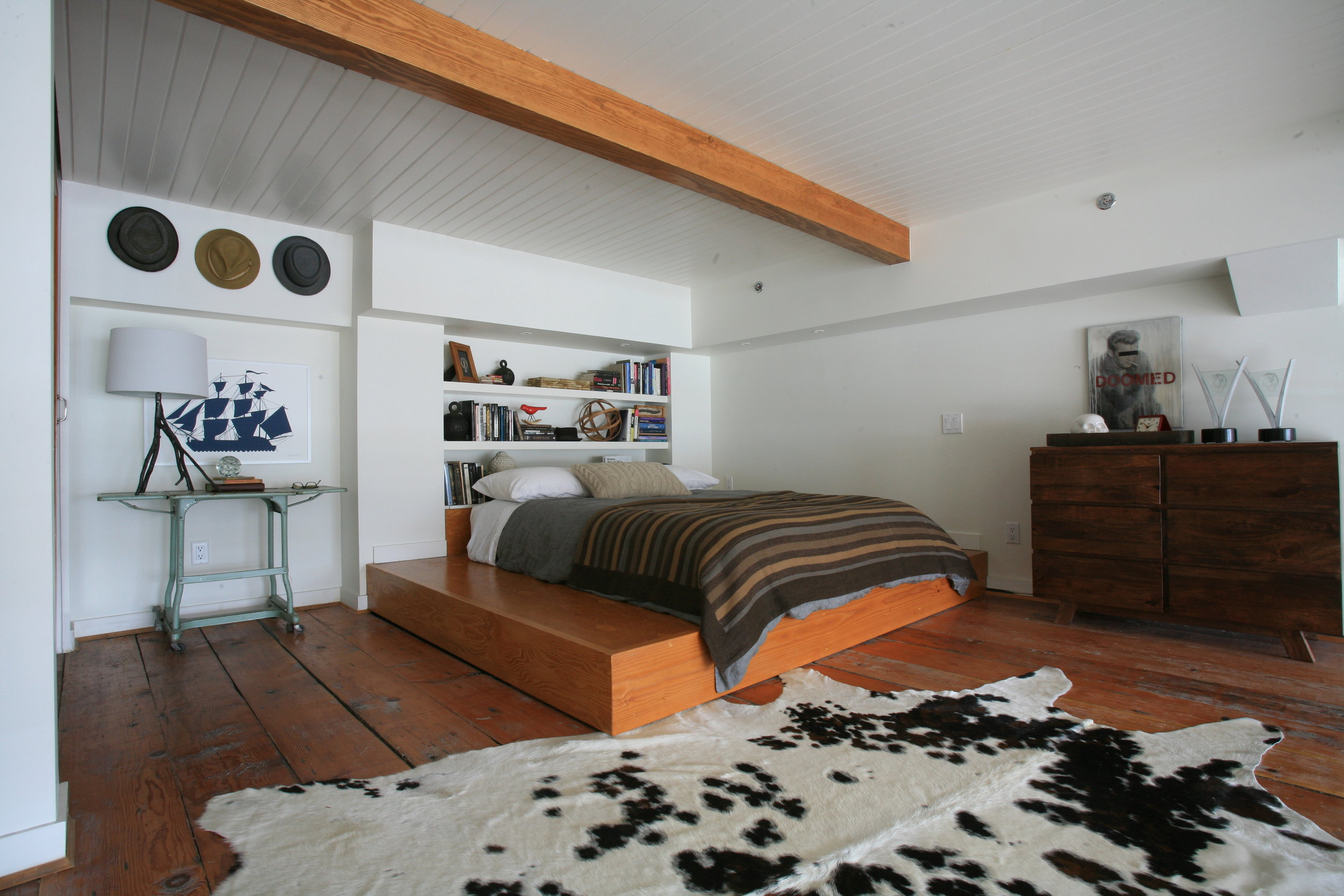 A low bed on a wooden platform with a large cow skin rug at the base of the bed and a headboard made out of shelves with books and decor collected on it beside a glass table and a dark wooden dresser.