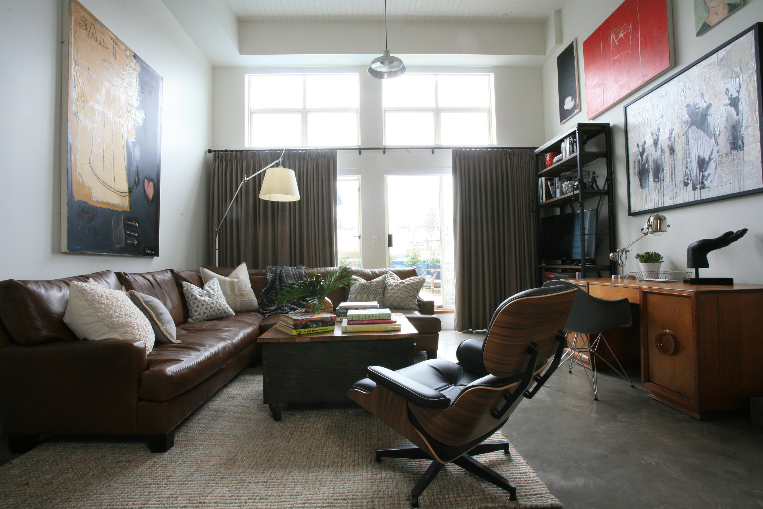 The living room of a loft, with masculine leather furniture and a home office, complete with various eclectic paintings on the wall.