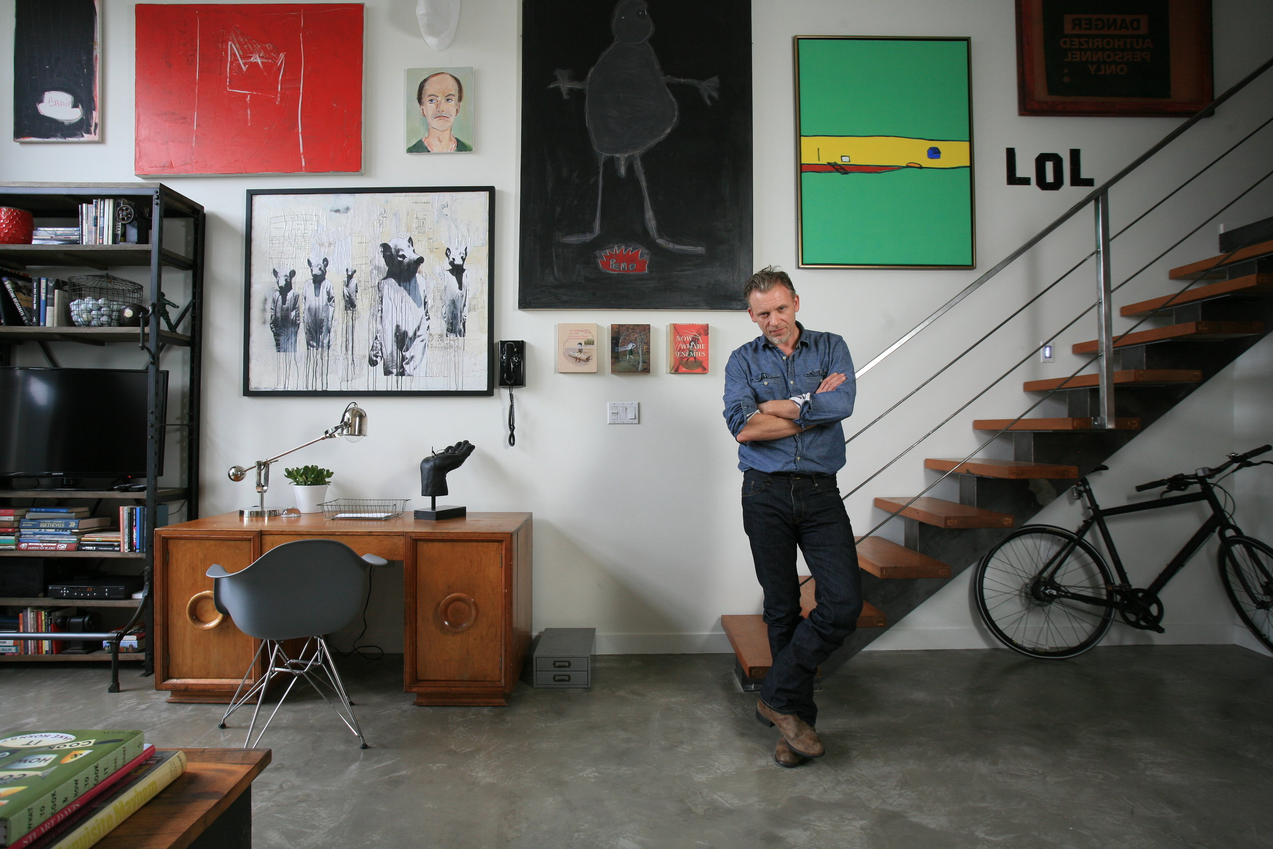 The homeowner stands in front of his wooden loft staircase, beside his home office and plethora of paintings on the wall.