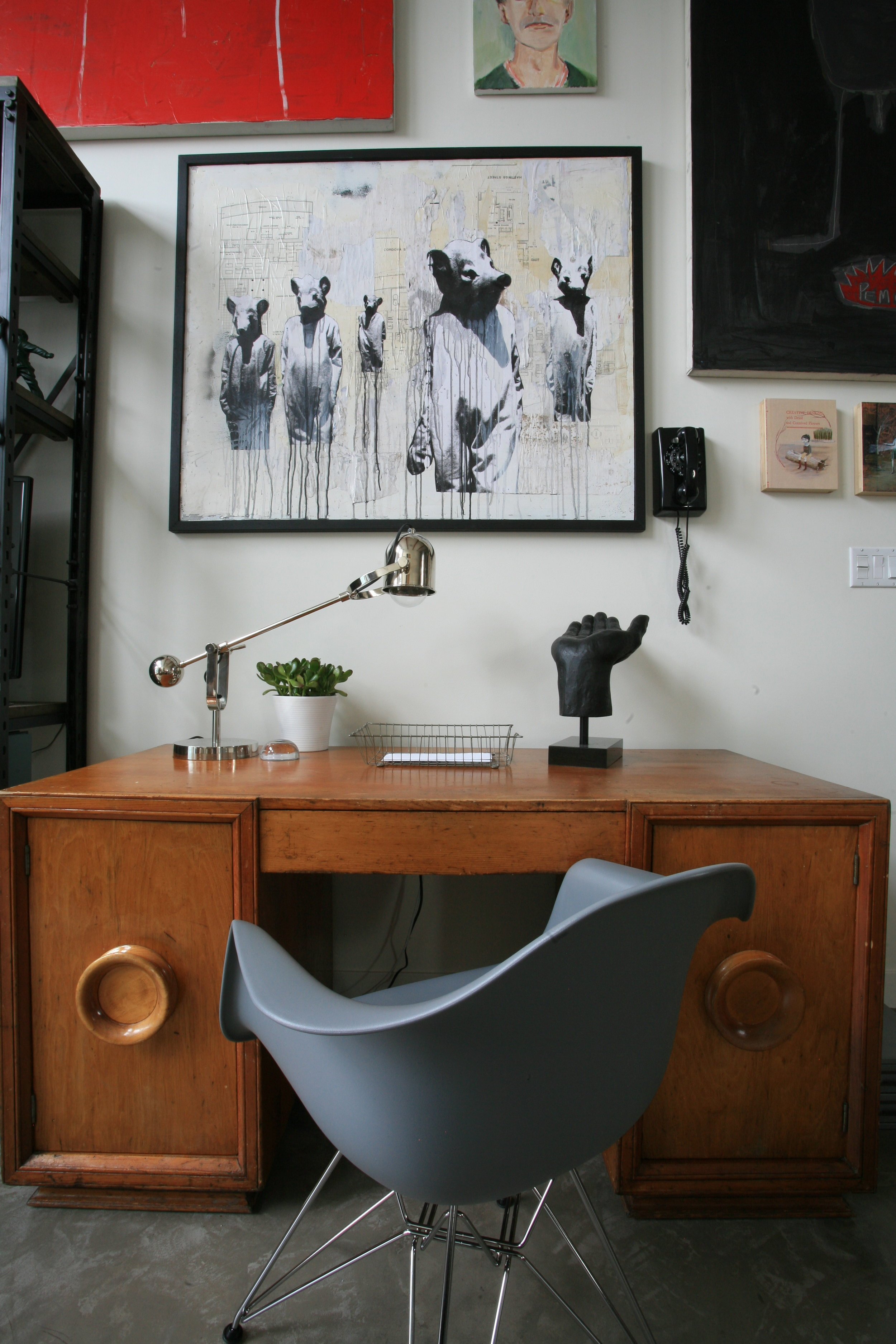 A collage of paintings and an old-timey phone hangs on the wall and an antique wooden desk with a mid-century style desk chair sit below the paintings. There are some items on the desk, including a silver lamp, a basket for letters and a statuette shaped like an open palm.
