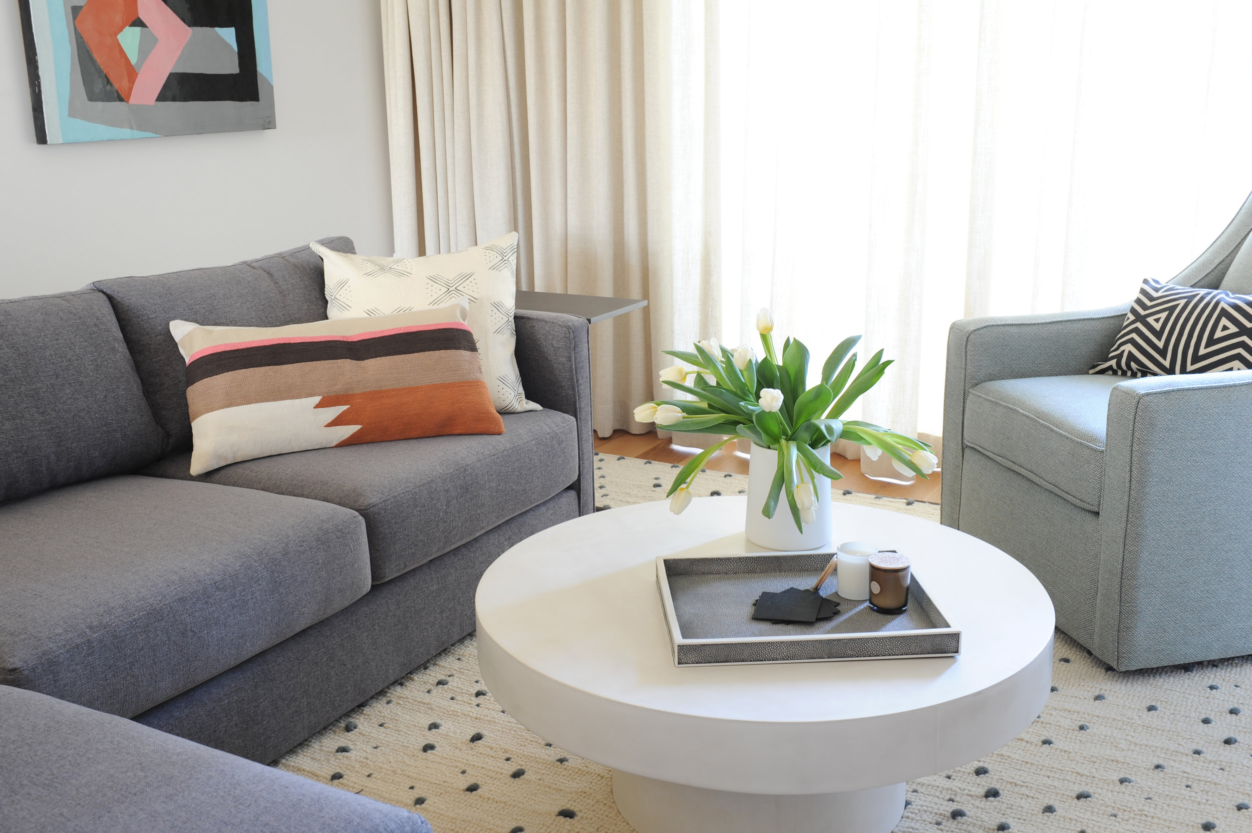 A white coffee table sits on a beige rug surrounded by a grey sectional and a light grey armchair.