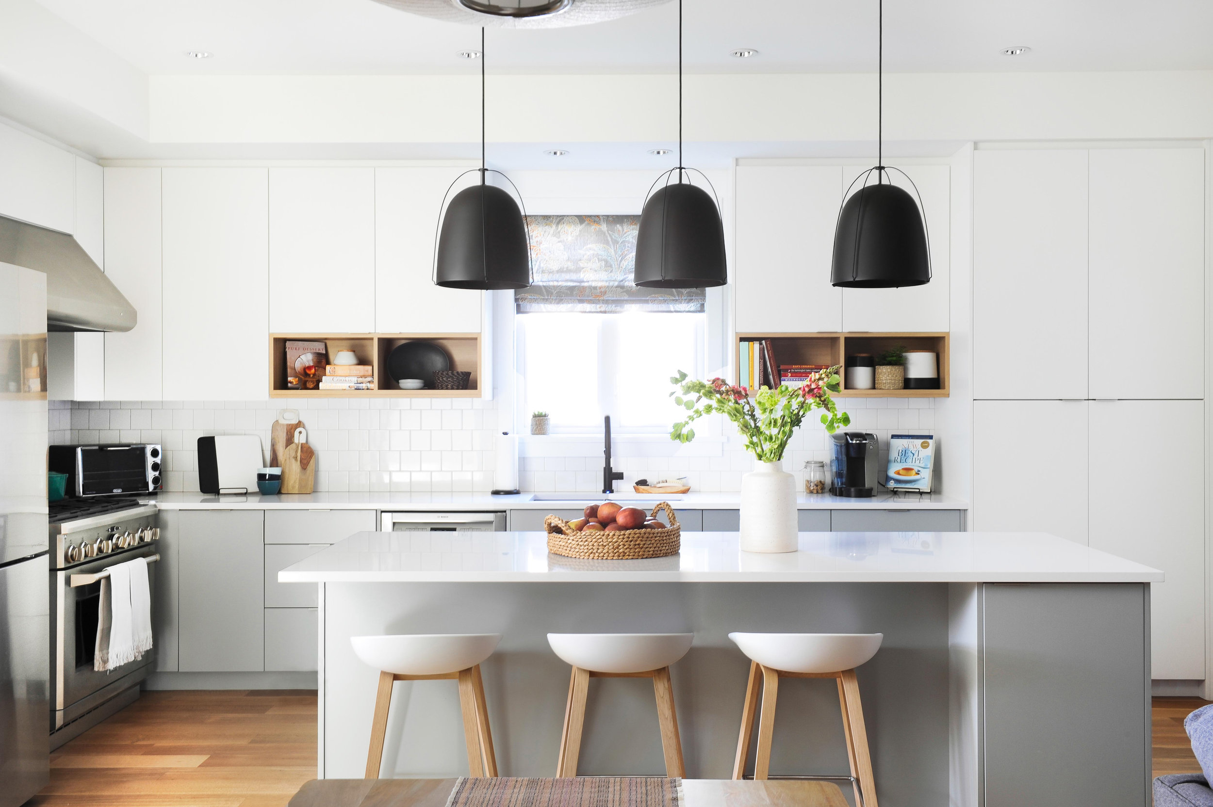 A white kitchen island and three modern white bar chairs sits in a modern family kitchen, with three large matte black lights hang above it.