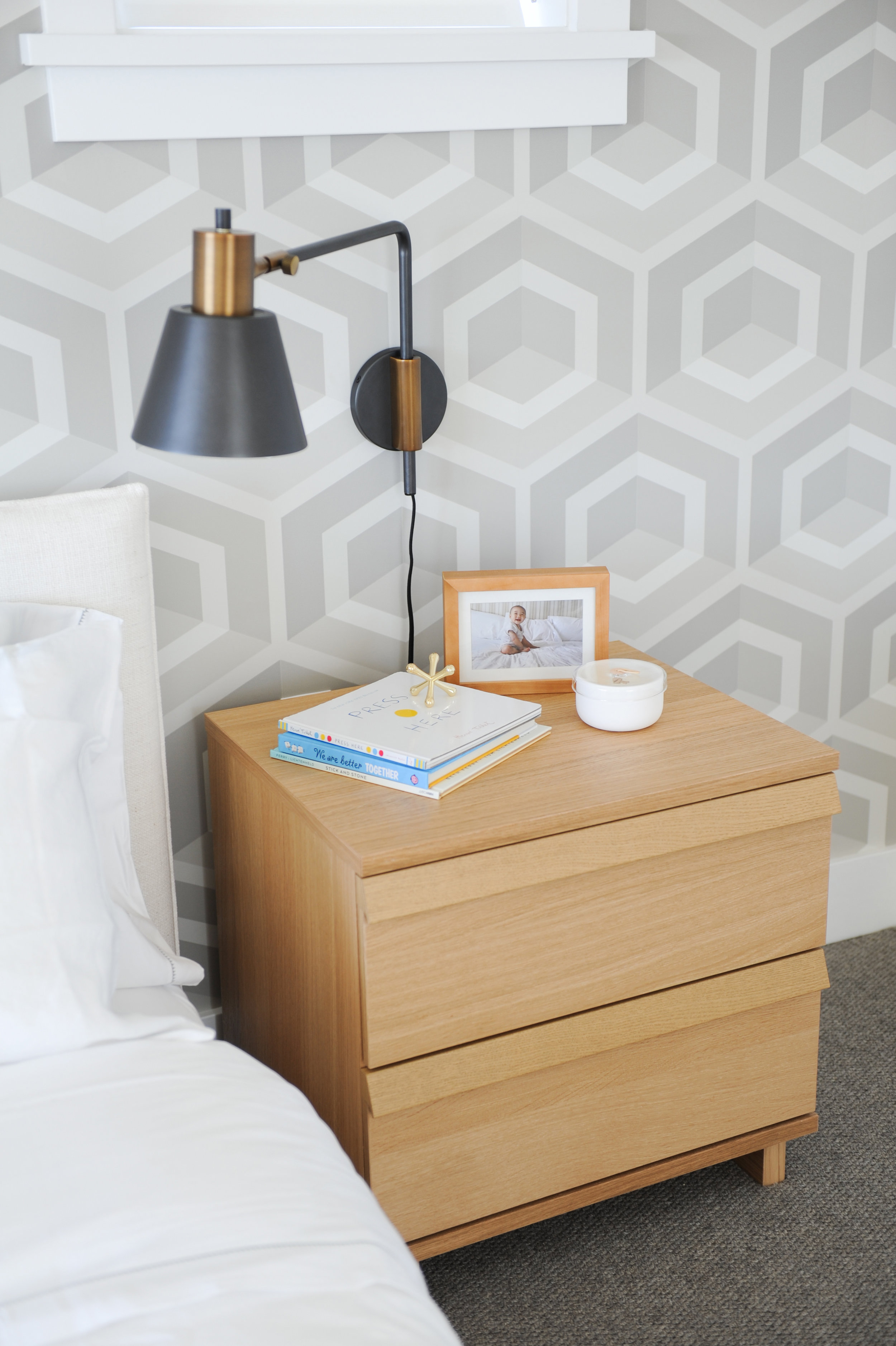 A brown wooden bedside table with a lamp, a book, a picture in a frame and a candle sat on top is directly underneath a windowsill.