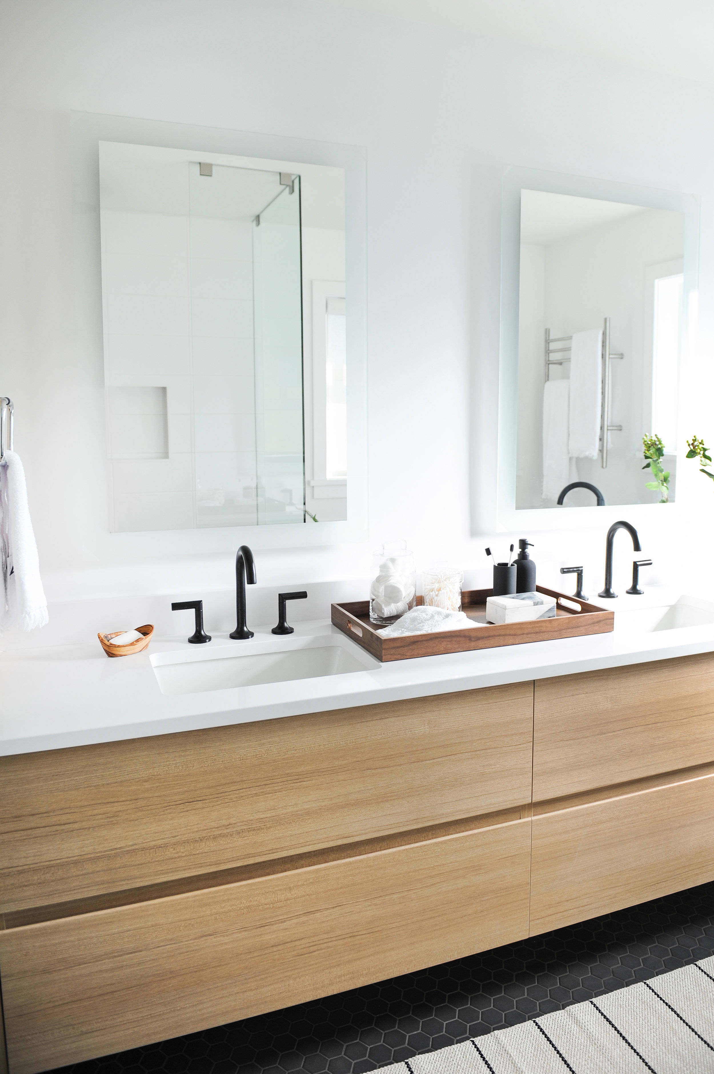 His and her sinks built into light wooden cabinets and a tray of various bathroom items sits in the middle