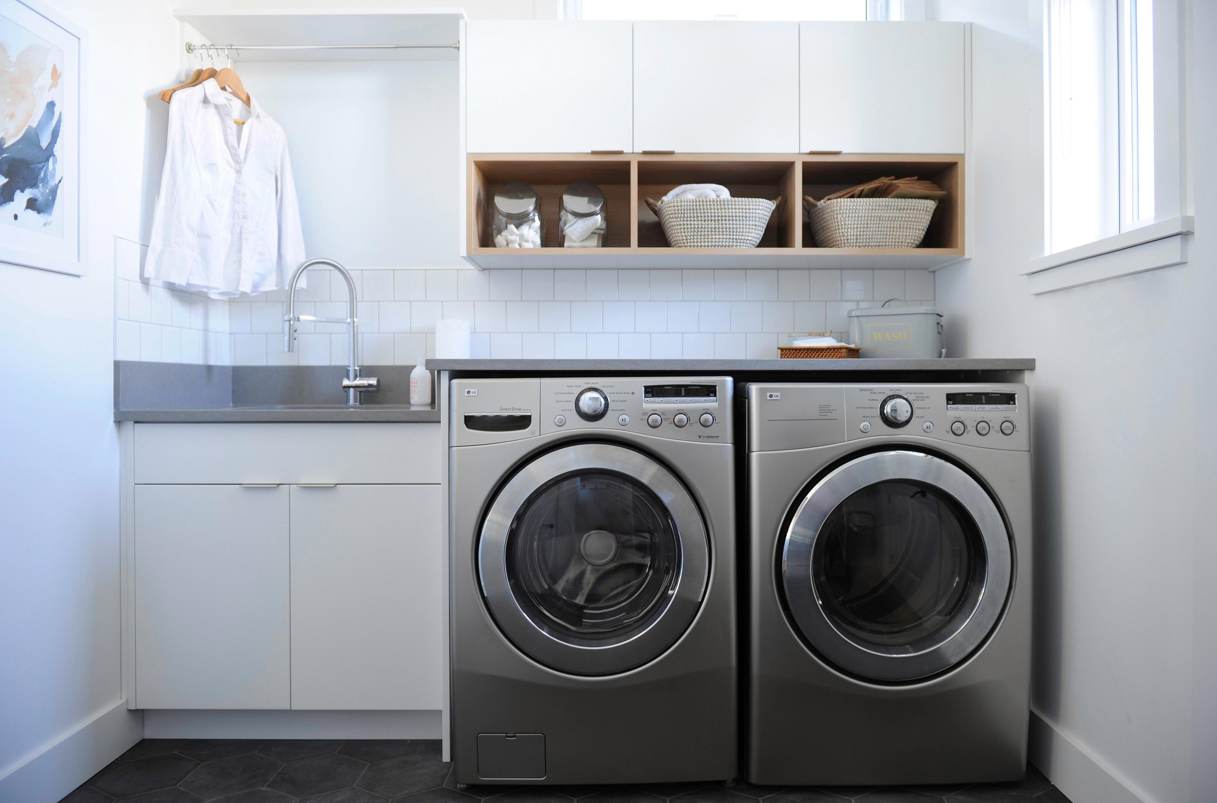 The laundry room, which contains a front loading washer and dryer, a sink and some shelving for baskets and soap.