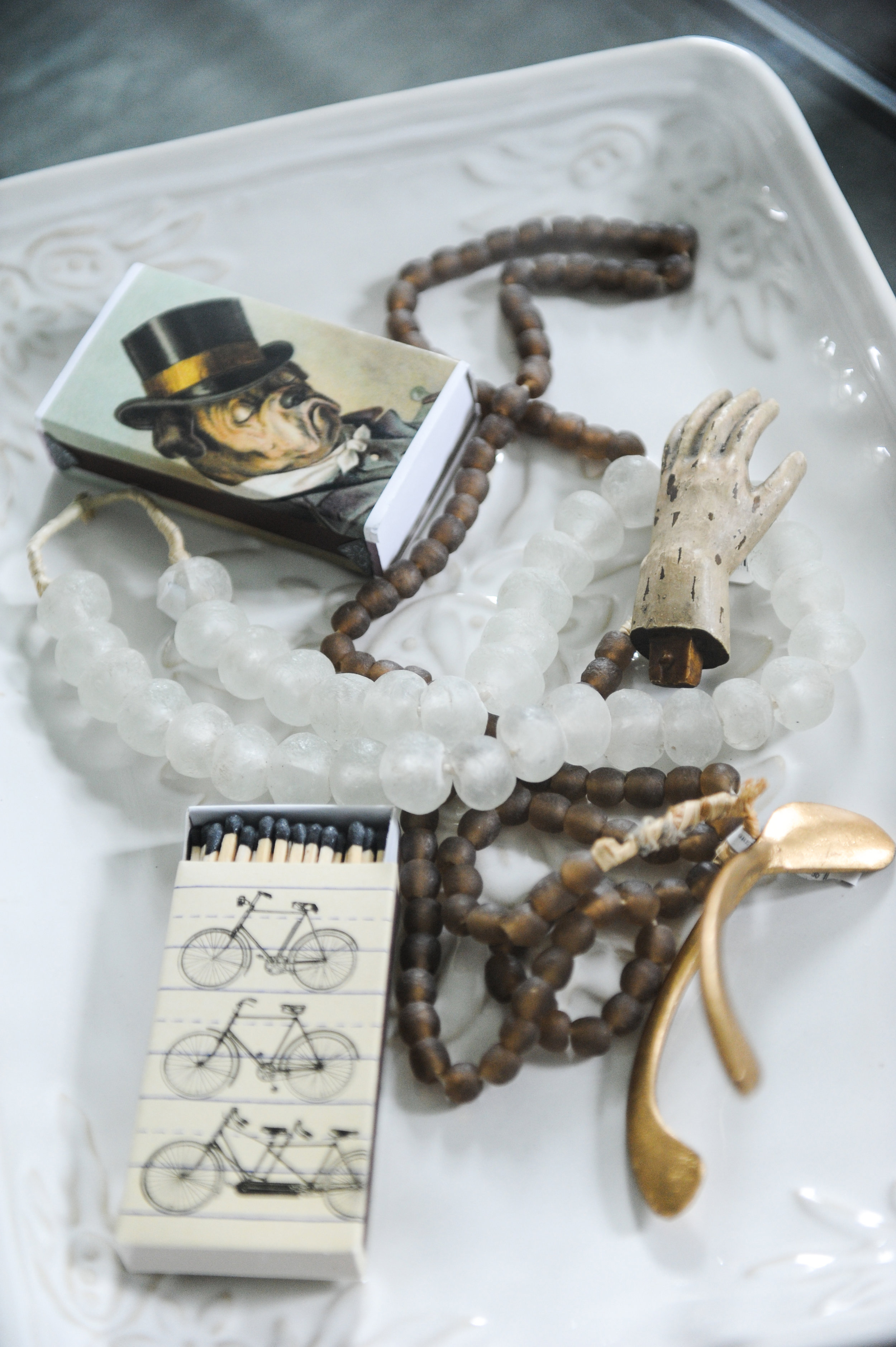 A white ceramic tray sits on a glass coffee table. There are various items on the tray, such as beaded necklaces, matchboxes, a golden wishbone and a tiny ceramic hand.